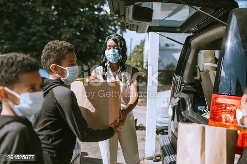 A family takes bags of groceries from the back of their vehicle, wearing protective face masks.  Either their own food or delivering to assist a friend or family member.  Part of the new routine during COVID-19 / Coronavirus pandemic.
