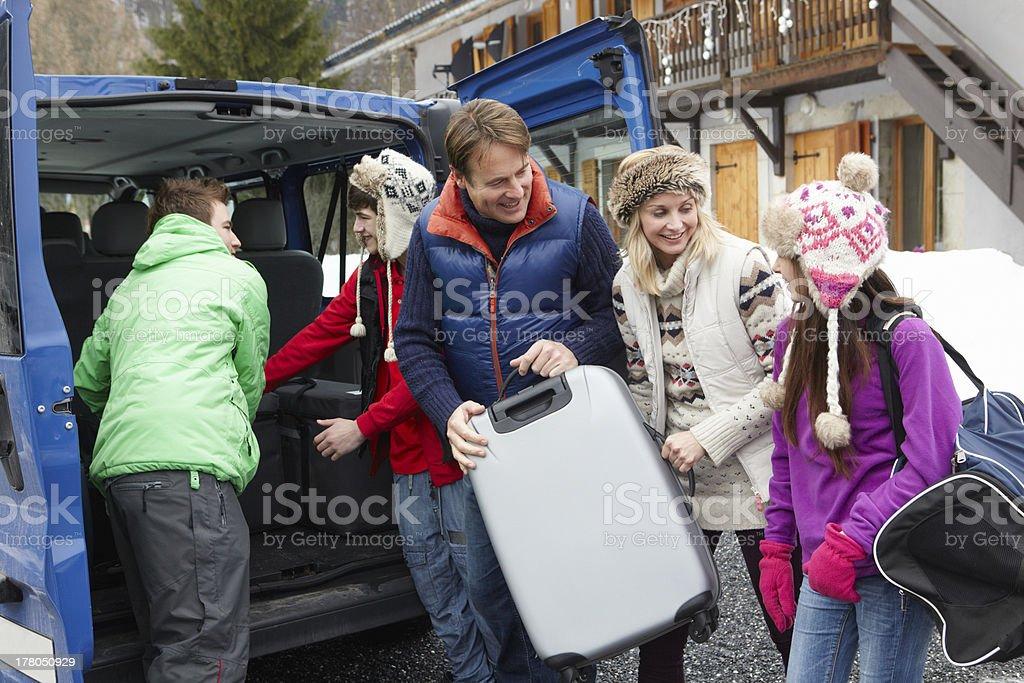 Family Unloading Luggage From Transfer Van Outside Chalet On Ski stock photo