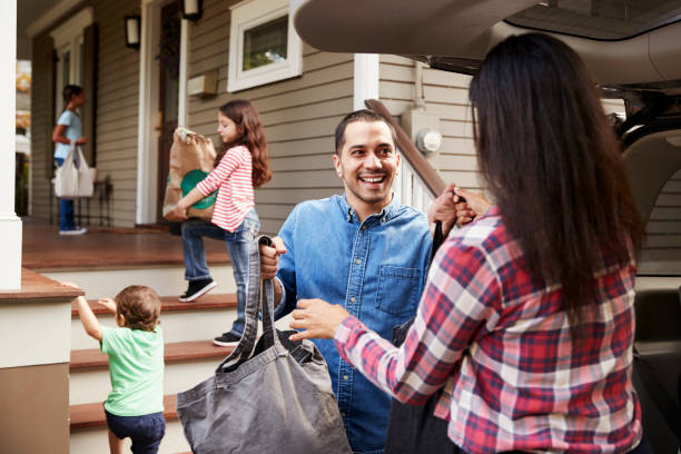 family unloading shopping bags from car - grocery home foto e immagini stock