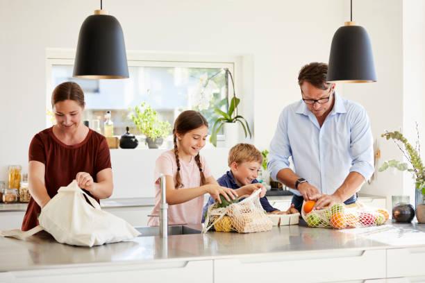 Familie packt Lebensmittel auf Kücheninsel aus – Foto