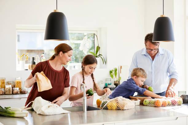 Familie packt Lebensmittel in der Küche zu Hause aus – Foto