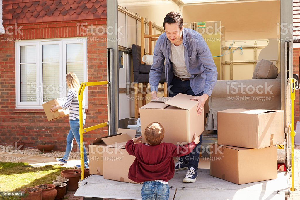 Family Unpacking Moving In Boxes From Removal Truck Family Unpacking Moving In Boxes From Removal Truck 2-3 Years Stock Photo