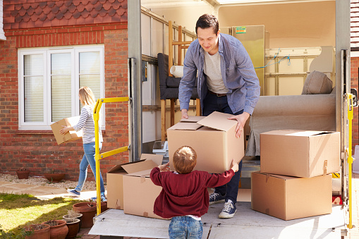 Family Unpacking Moving In Boxes From Removal Truck Stock Photo - Download Image Now