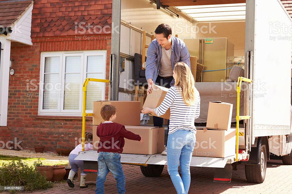 Family Unpacking Moving In Boxes From Removal Truck stock photo
