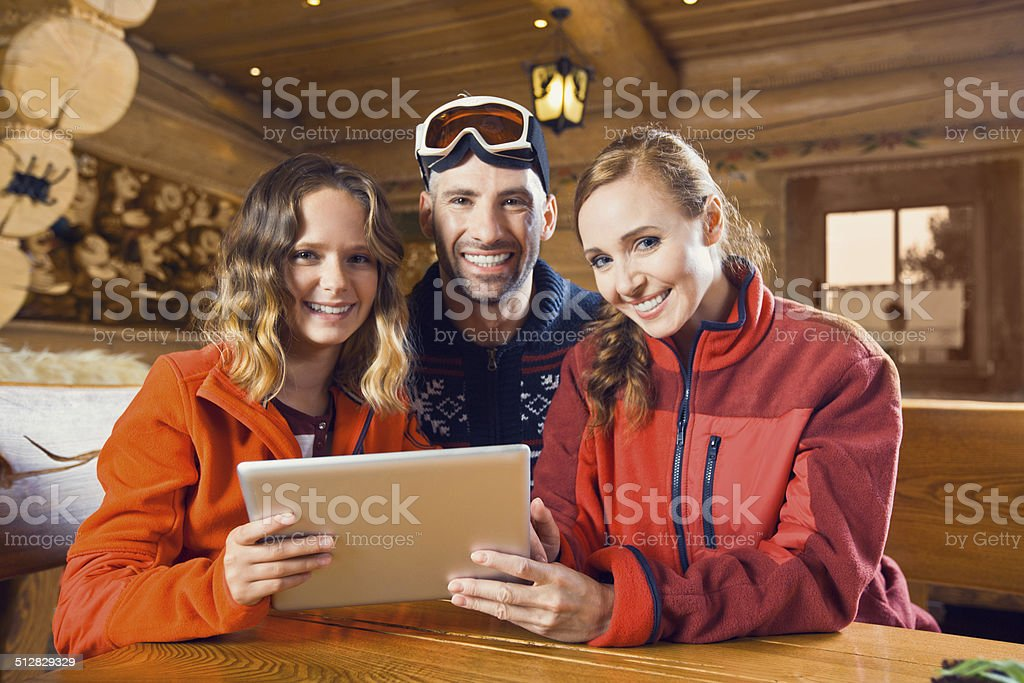 Family using digital tablet Happy mother, father and daughter sitting in a mountain restaurant after skiing and using a digital tablet together, smiling at the camera. Adolescence Stock Photo