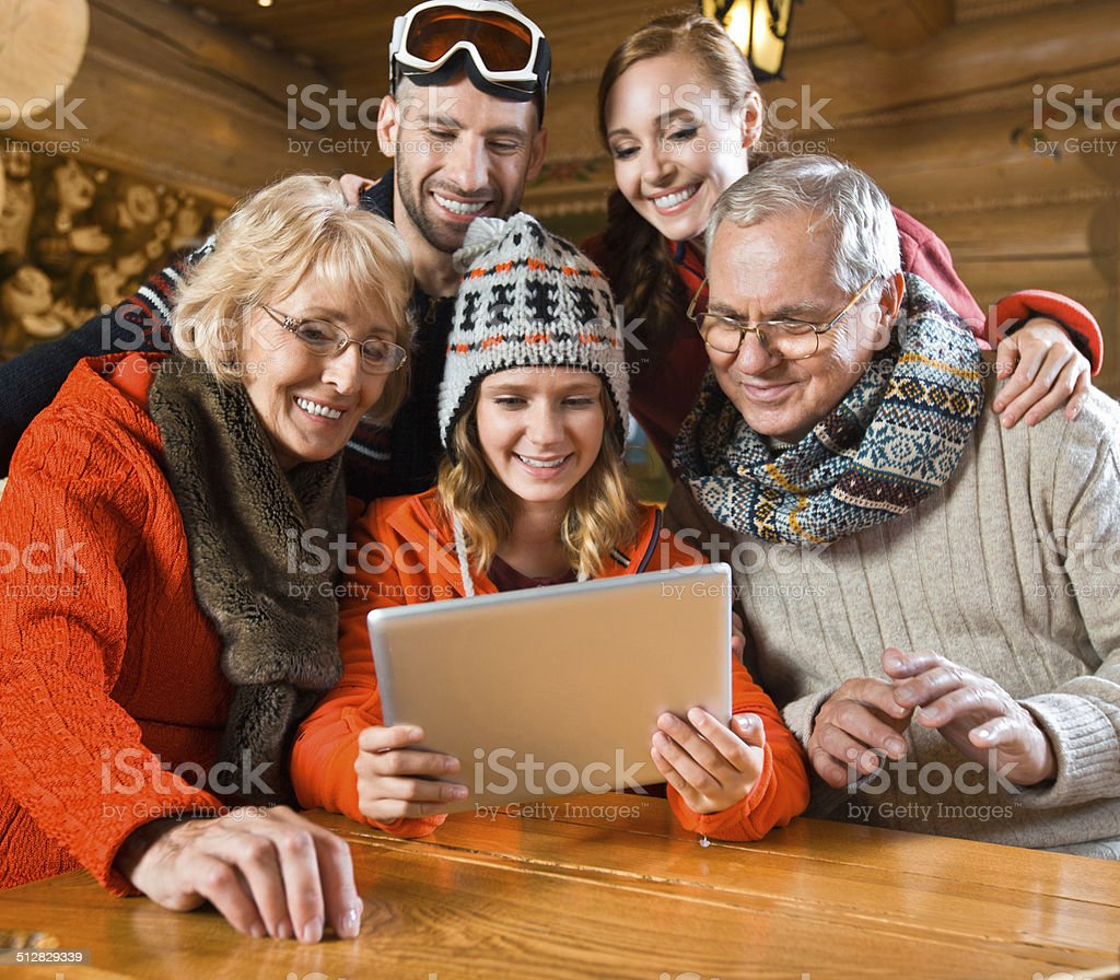 Family using digital tablet Multi-generation family sitting in a mountain restaurant after skiing and using a digital tablet together. Active Seniors Stock Photo