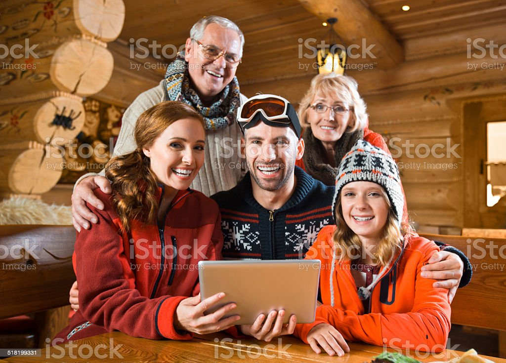 Family using digital tablet Multi-generation family sitting in a mountain restaurant after skiing and using a digital tablet together, smiling at the camera. Active Seniors Stock Photo
