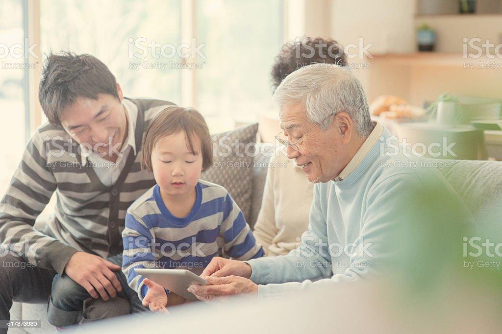 デジタルタブレットご家族とご一緒に自宅 - 30代のロイヤリティフリーストックフォト