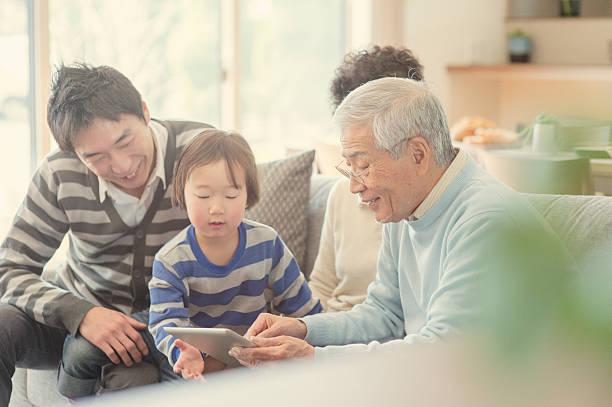 デジタルタブレットご家族とご一緒に自宅 - 家族 日本人 ストックフォトと画像