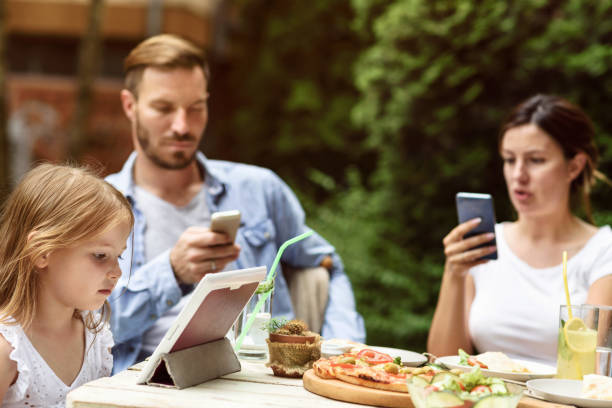 Family using digital technology at a lunch table Boredom, Family not talking, surfing internet and texting serbia and montenegro stock pictures, royalty-free photos & images