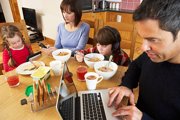 family using gadgets whilst eating breakfast together in kitchen - eating technology stock photos and pictures