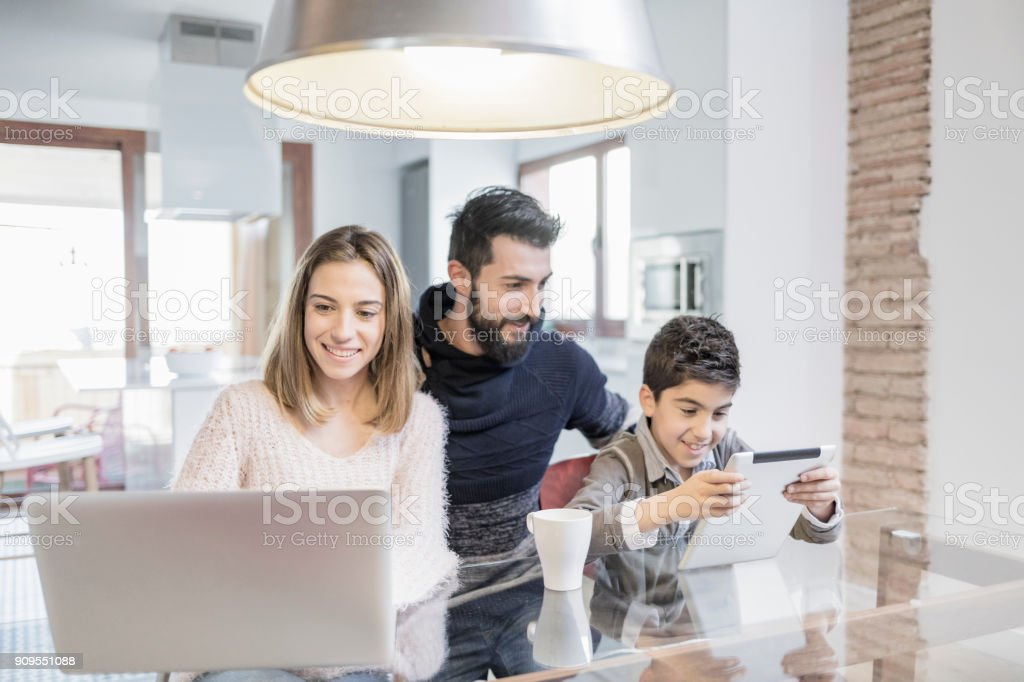 Family using laptop and tablet in the kitchen stock photo