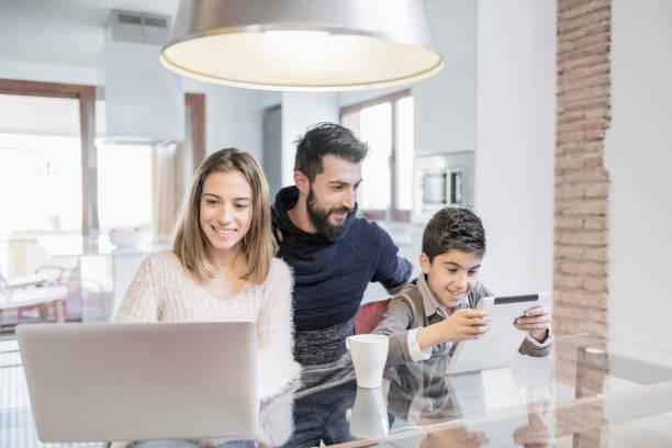 Famille en utilisant l'ordinateur portable et tablette dans la cuisine - Photo