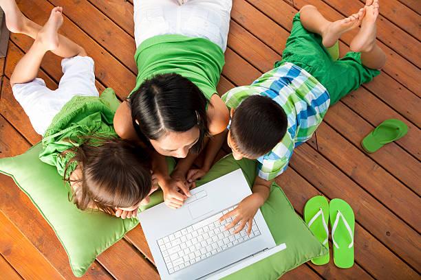 familie mit laptop auf deck - garden types stock-fotos und bilder