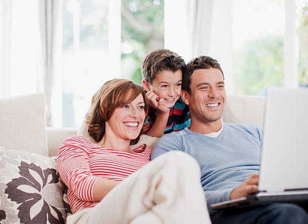 family using laptop on sofa together - 30 39 years stock photos and pictures