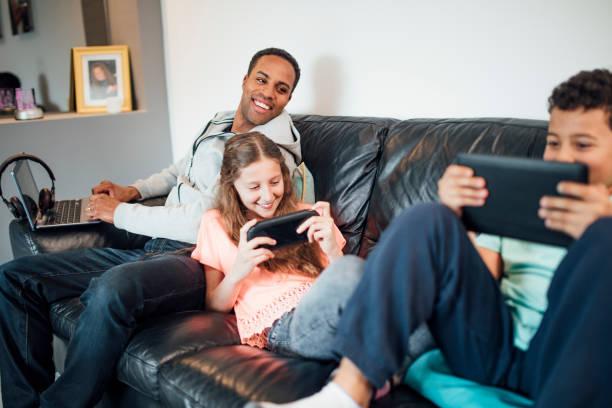 tecnología en casa de familia - padre que se queda en casa fotografías e imágenes de stock