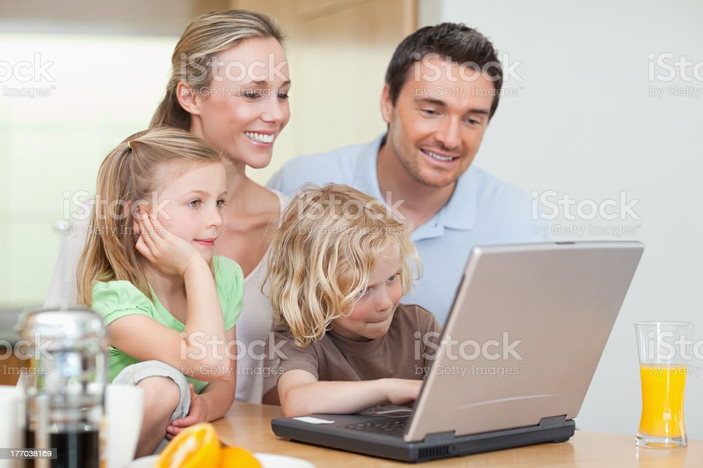 Family using their laptop in the kitchen Family using the internet in the kitchen together 30-39 Years Stock Photo