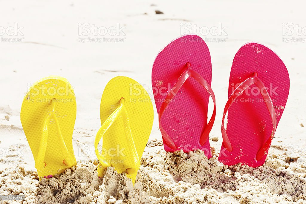 Family vacation: big and small flipflops on sandy, sunny beach stock photo