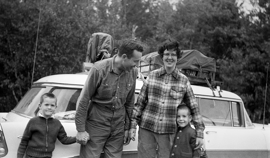 Car packed and ready to go in background for family vacation in 1957, Family of parents and two boys in front.