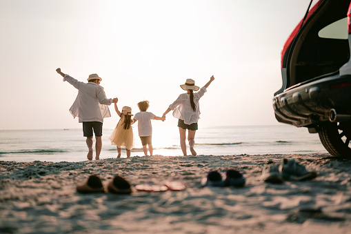 Family vacation holiday, Happy family running on the beach in the sunset. Back view of a happy family on a tropical beach and a car on the side.