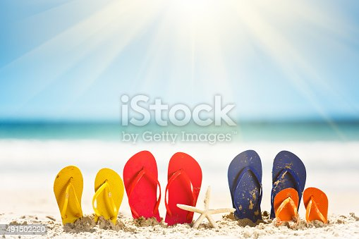Let the family vacation fun begin! Two pairs of adult flipflop rubber sandals and two in children's sizes sit on a sandy beach with calm sea in the background. Lens flare off the hot, summer sun and copy space on the sky.
