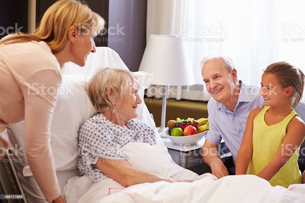 Family Visit To Grandmother In Hospital Bed stock photo
