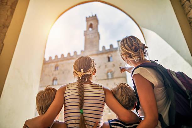 family visiting italian town of volterra, tuscany - toskana ferien stock-fotos und bilder