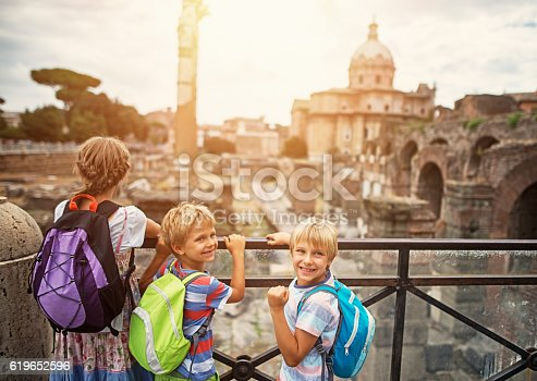 Mother and kids visiting Rome. Excited kids are looking at magnificient Roman Forum.