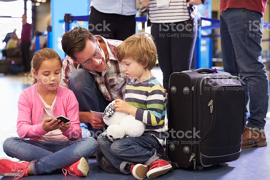 Family Wait In Queue At Airport Check In stock photo