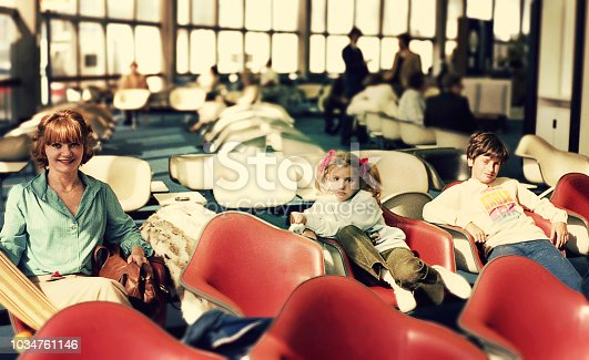 Vintage image of a mother and her children waiting at the airport.
