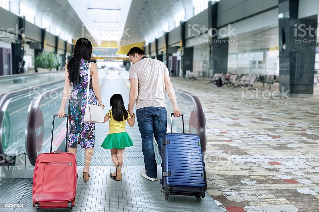 Family walk in airport hall stock photo