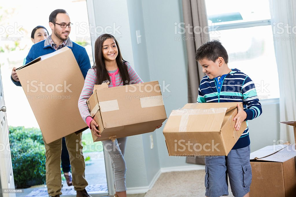 Family walk into their new home with boxes stock photo