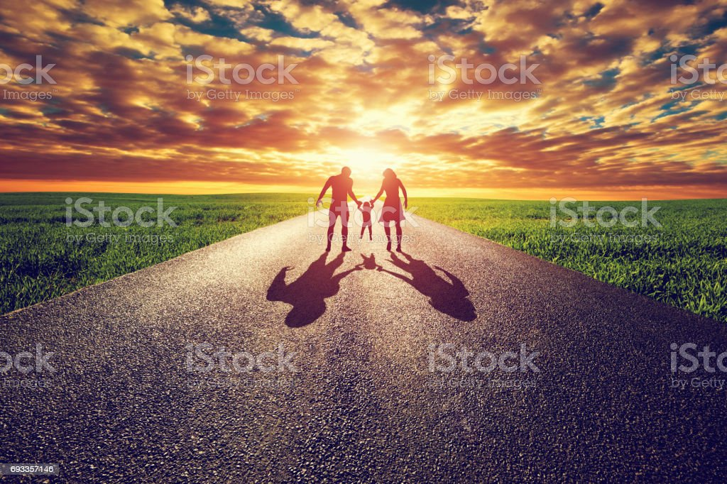 Family walk on long straight road, way towards sunset sun stock photo