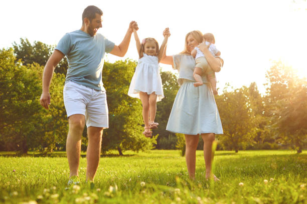Family walk with a child at sunset on the nature stock photo