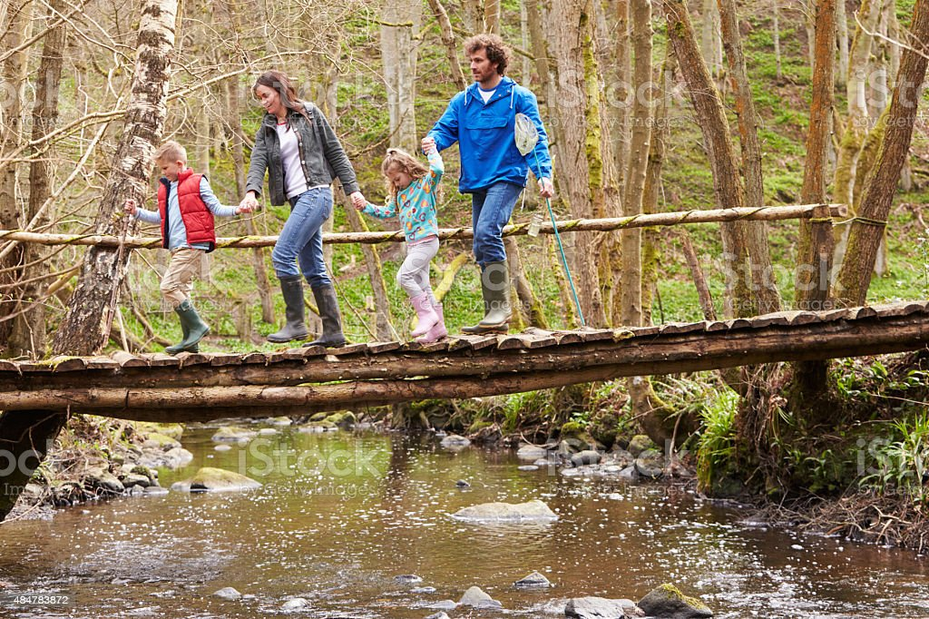 Family Walking Across Wooden Bridge Over Stream In Forest stock photo