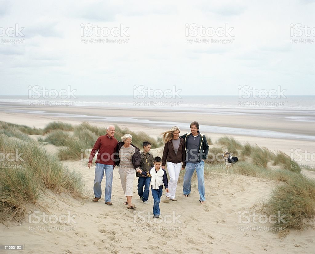 Family walking along a beach stock photo