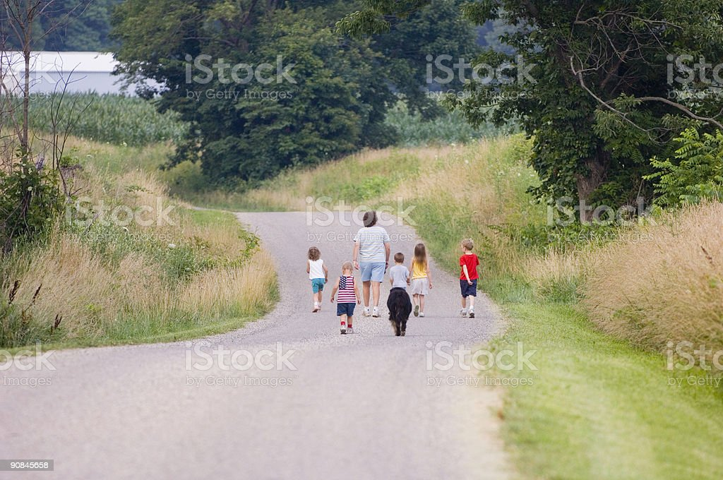Family walking along a country road royalty-free stock photo