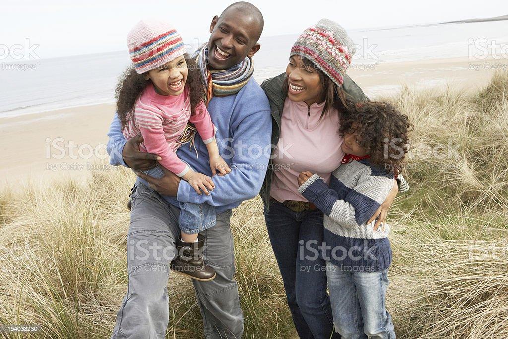 Family Walking Along Dunes On Winter Beach stock photo