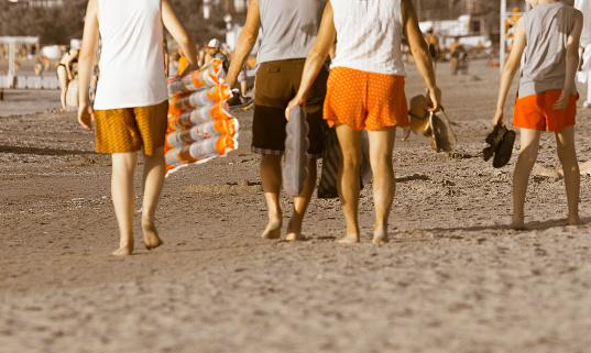 family walking along sandy beach