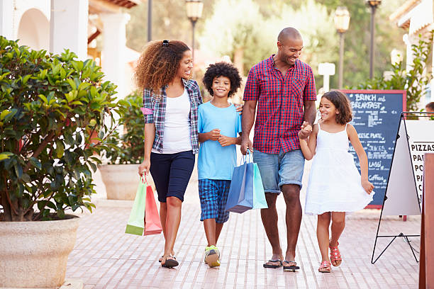 Family Walking Along Street With Shopping Bags stock photo