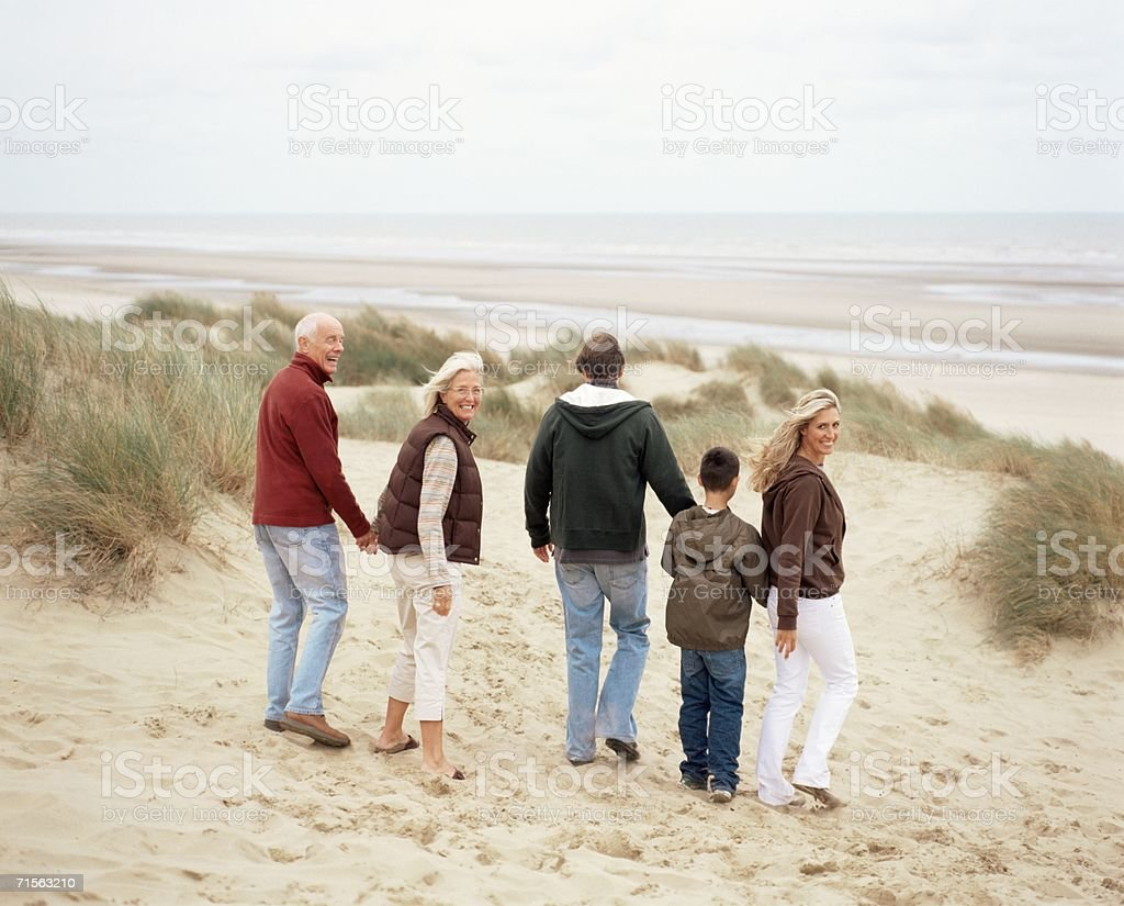 Family walking along the beach stock photo