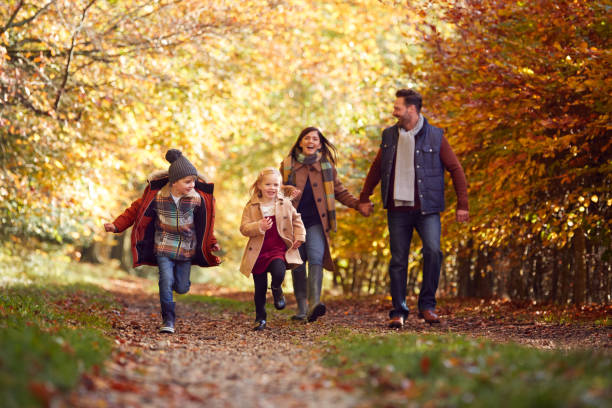 Family Walking Along Track In Autumn Countryside With Children Running Ahead stock photo