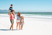 Smiling parents with children at beach. Cute son sitting on father shoulder with mother and sister walking while talking. Happy family with two children enjoying summer holiday at beach with copy space.