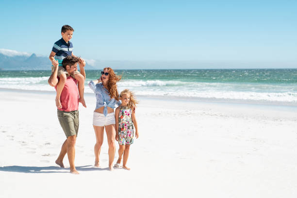 Family walking at beach Smiling parents with children at beach. Cute son sitting on father shoulder with mother and sister walking while talking. Happy family with two children enjoying summer holiday at beach with copy space. piggyback stock pictures, royalty-free photos & images