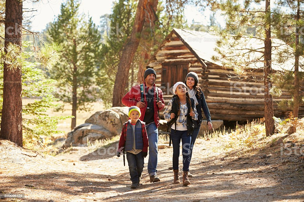 Family walking away from a log cabin in a forest stock photo