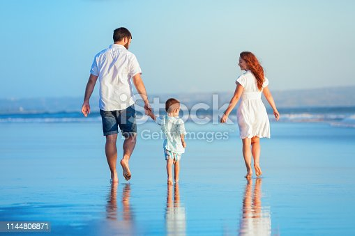 849648098 istock photo Family walking by sunset beach 1144806871