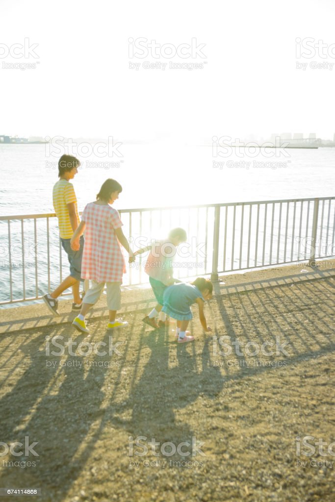 Family walking hand in hand from behind royalty-free stock photo