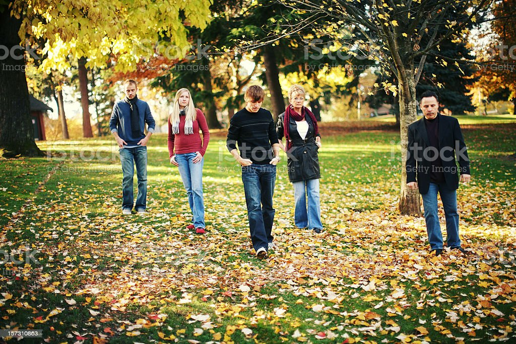 Family Walking in Autumn Leaves at Park royalty-free stock photo