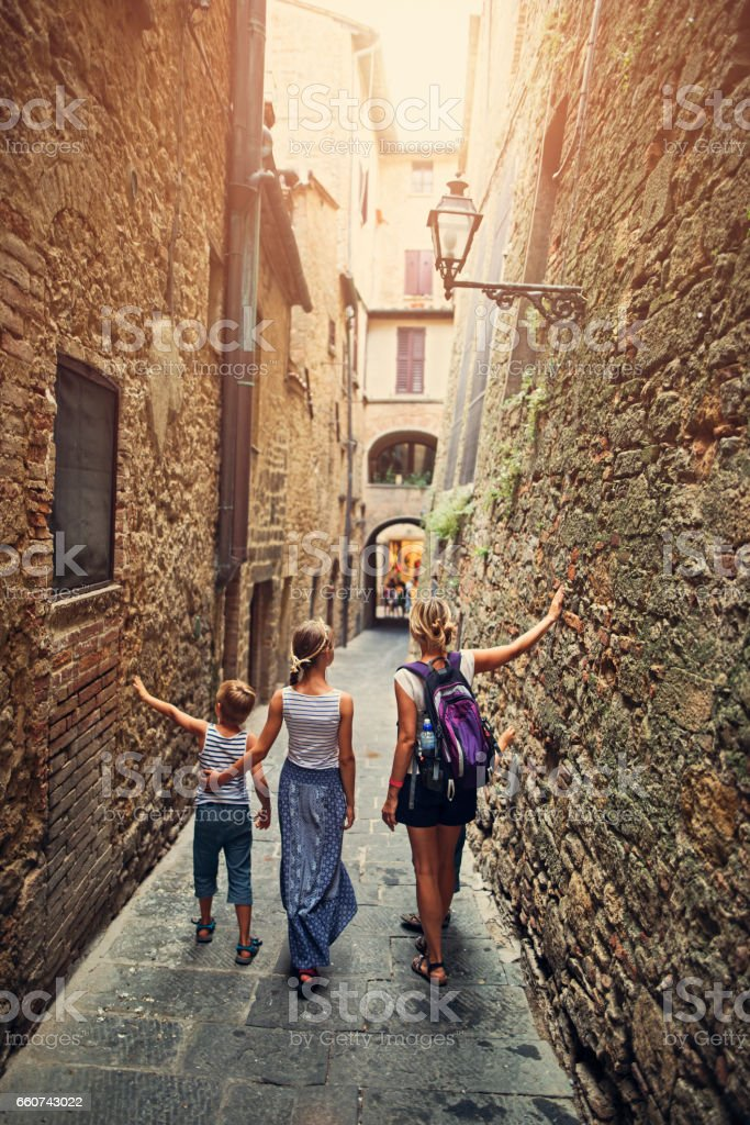 Family walking in back street of Volterra, Tuscany, Italy stock photo