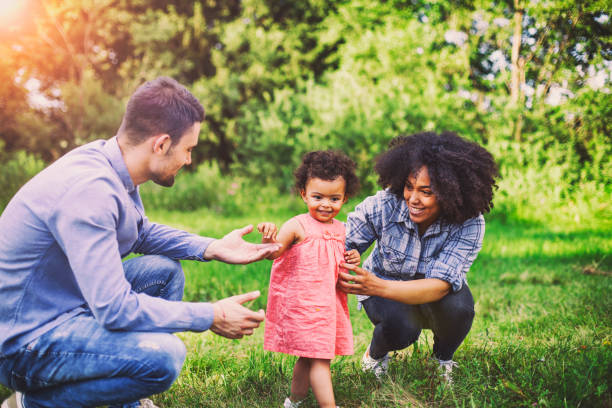 Family Walking In Field Carrying Young Baby Girl stock photo
